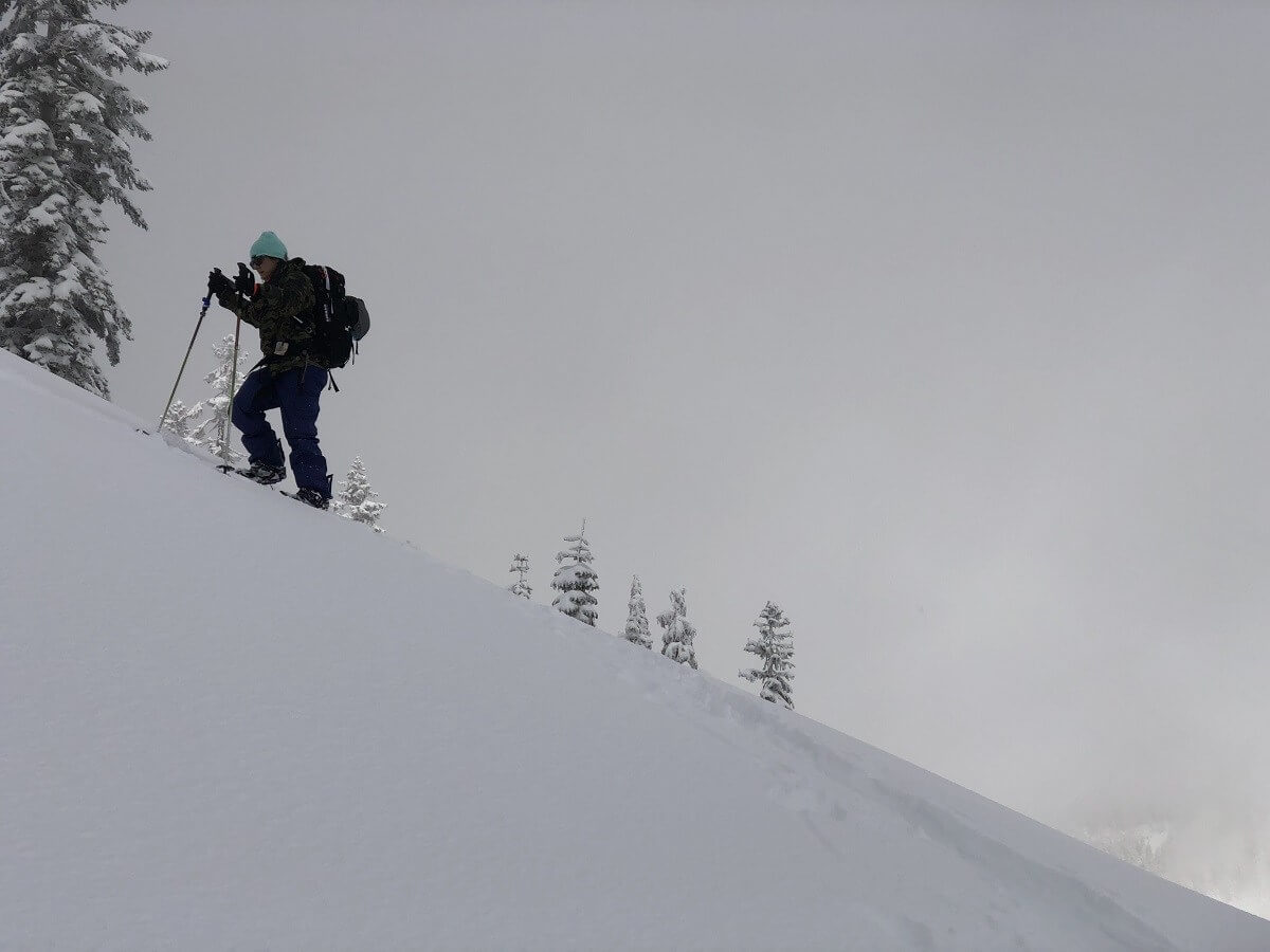 splitboarder climbing up a slope in Lassen National Park on a snowy day