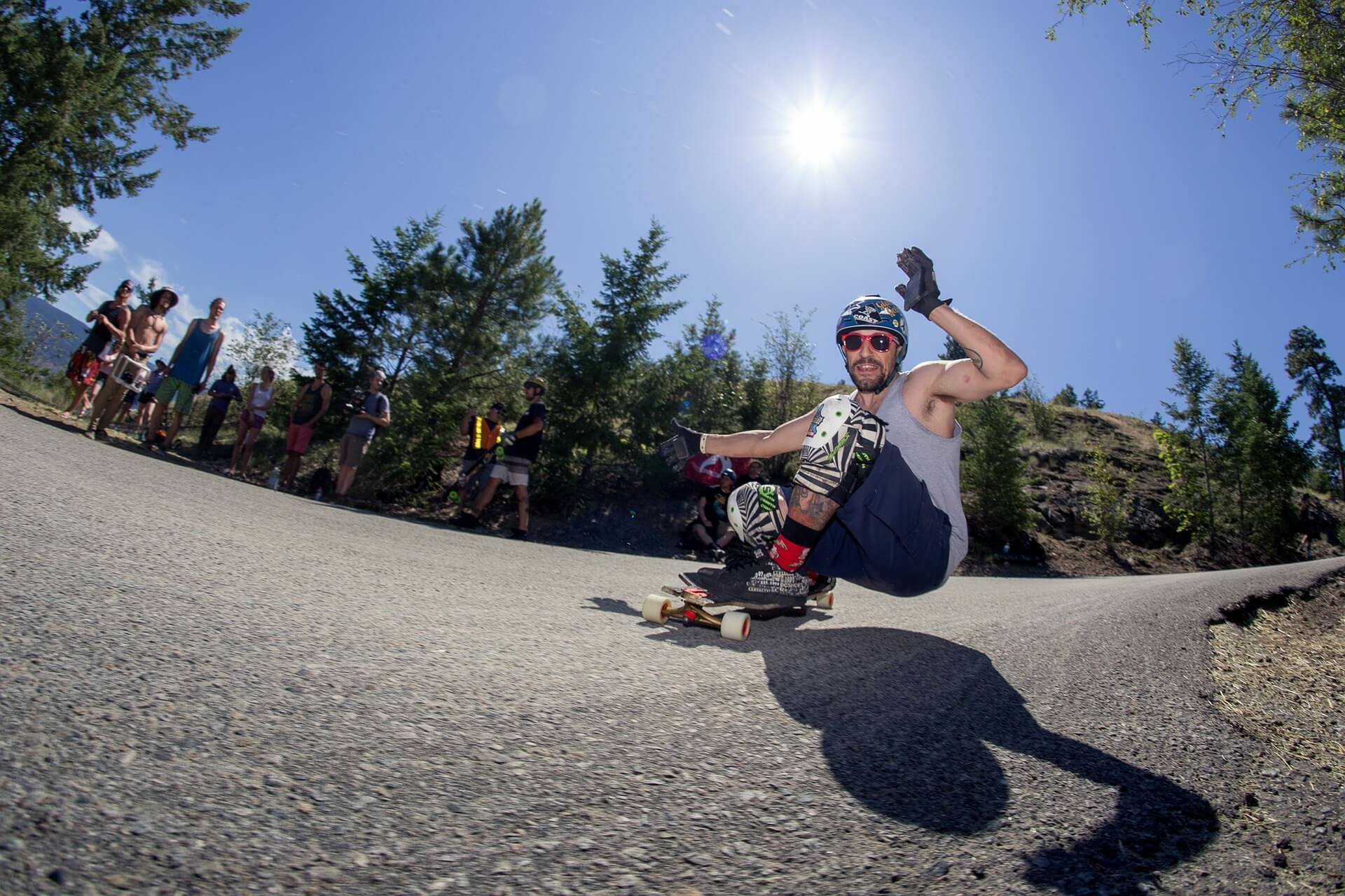 person longboarding on a downhill road