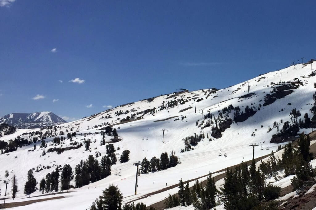 Sunny summer weather at Mammoth Mountain with snow corn conditions