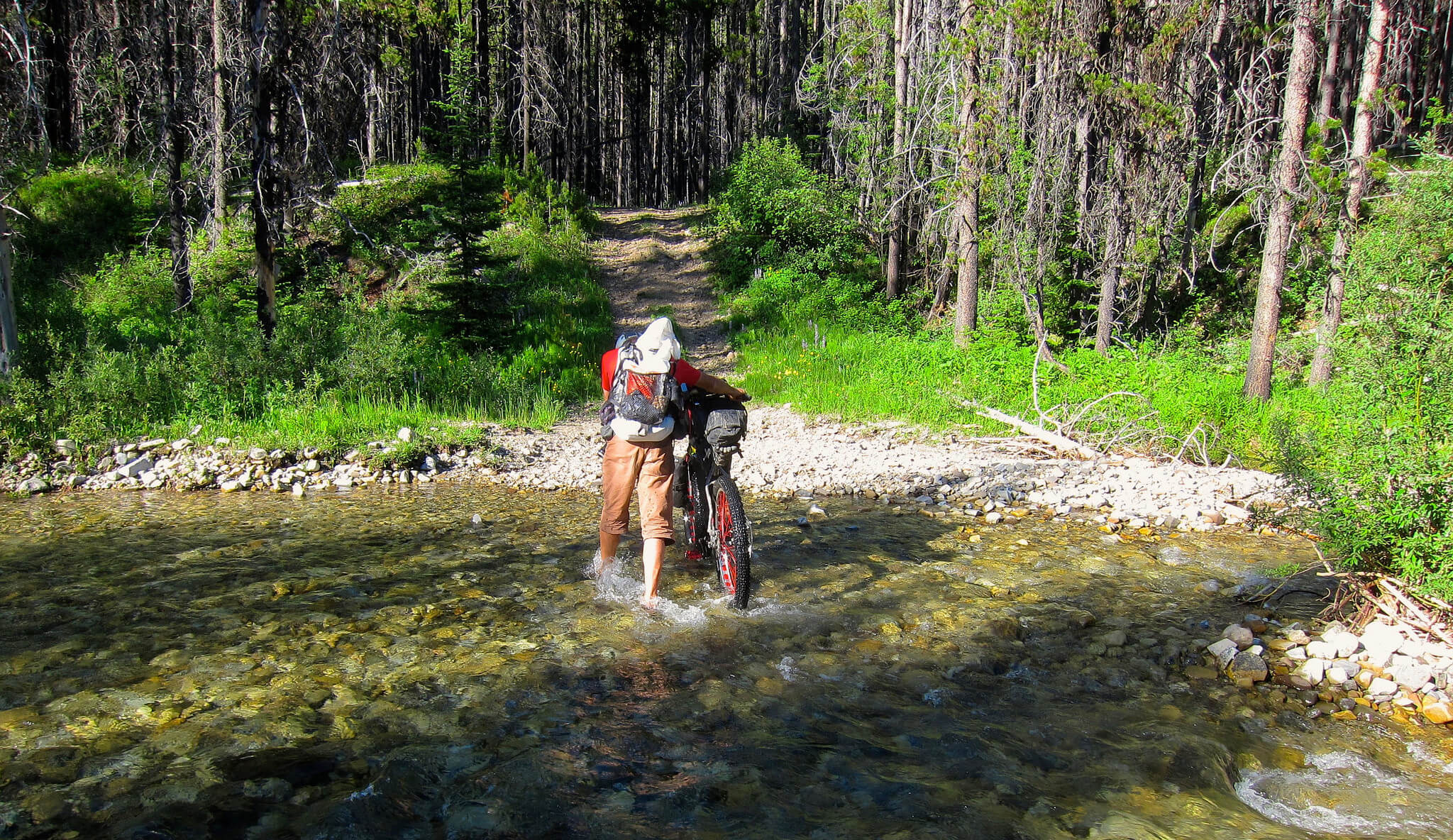 person fording a river on Tour The Divide