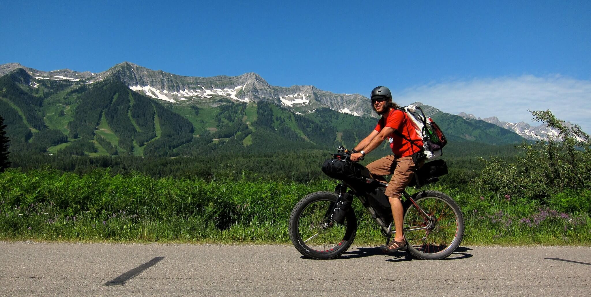 Person riding past Fernie on Tour the Divide showcasing one of the 3 types of outdoor activities