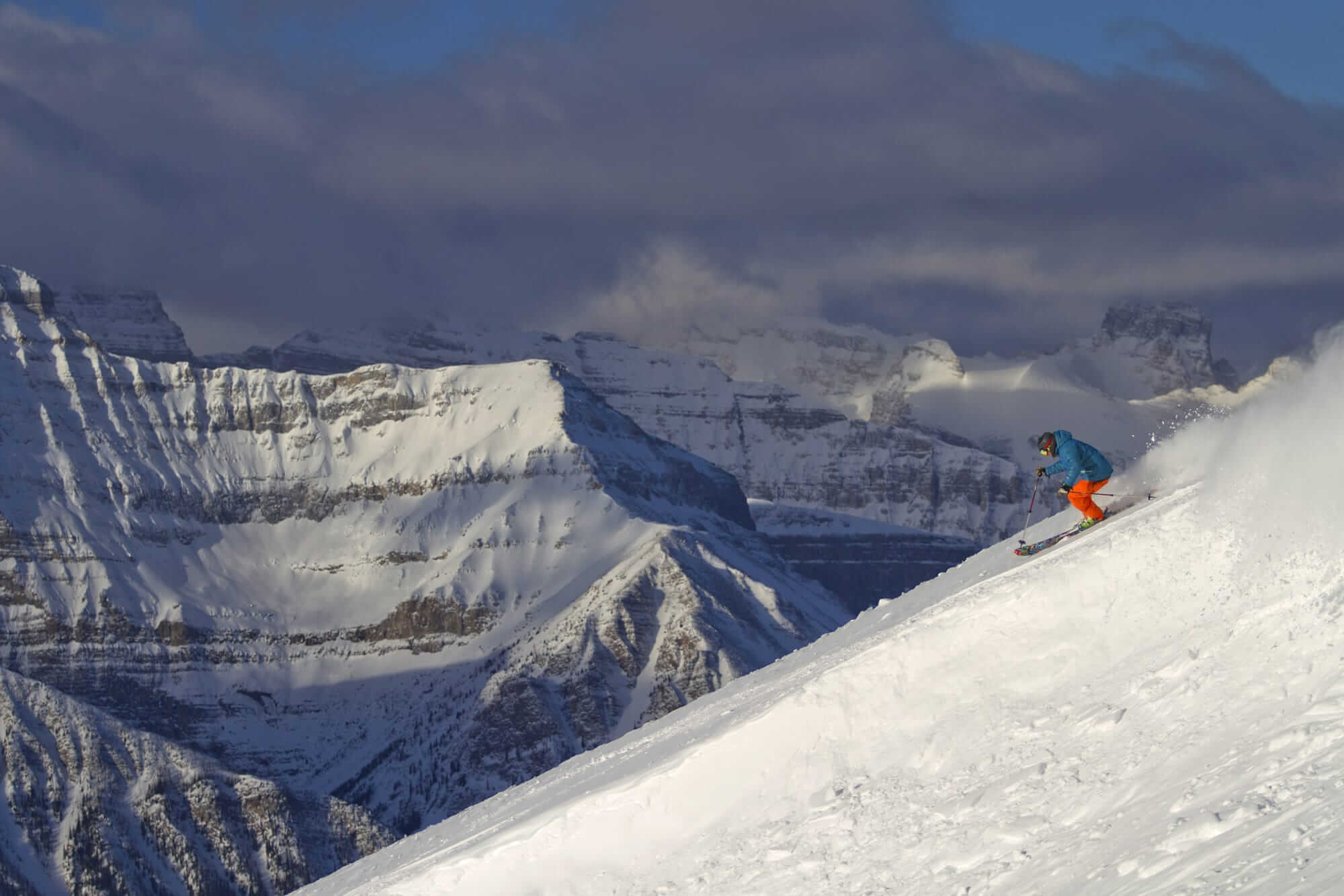 skier carving soft snow with Canadian Rockies behind him