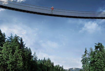 Woman crossing Treetops Adventure series of suspension bridges with canyon lights Capilano Suspension Bridge above the Capilano River Capilano Suspension Bridge Park Best Suspension Bridges in North America