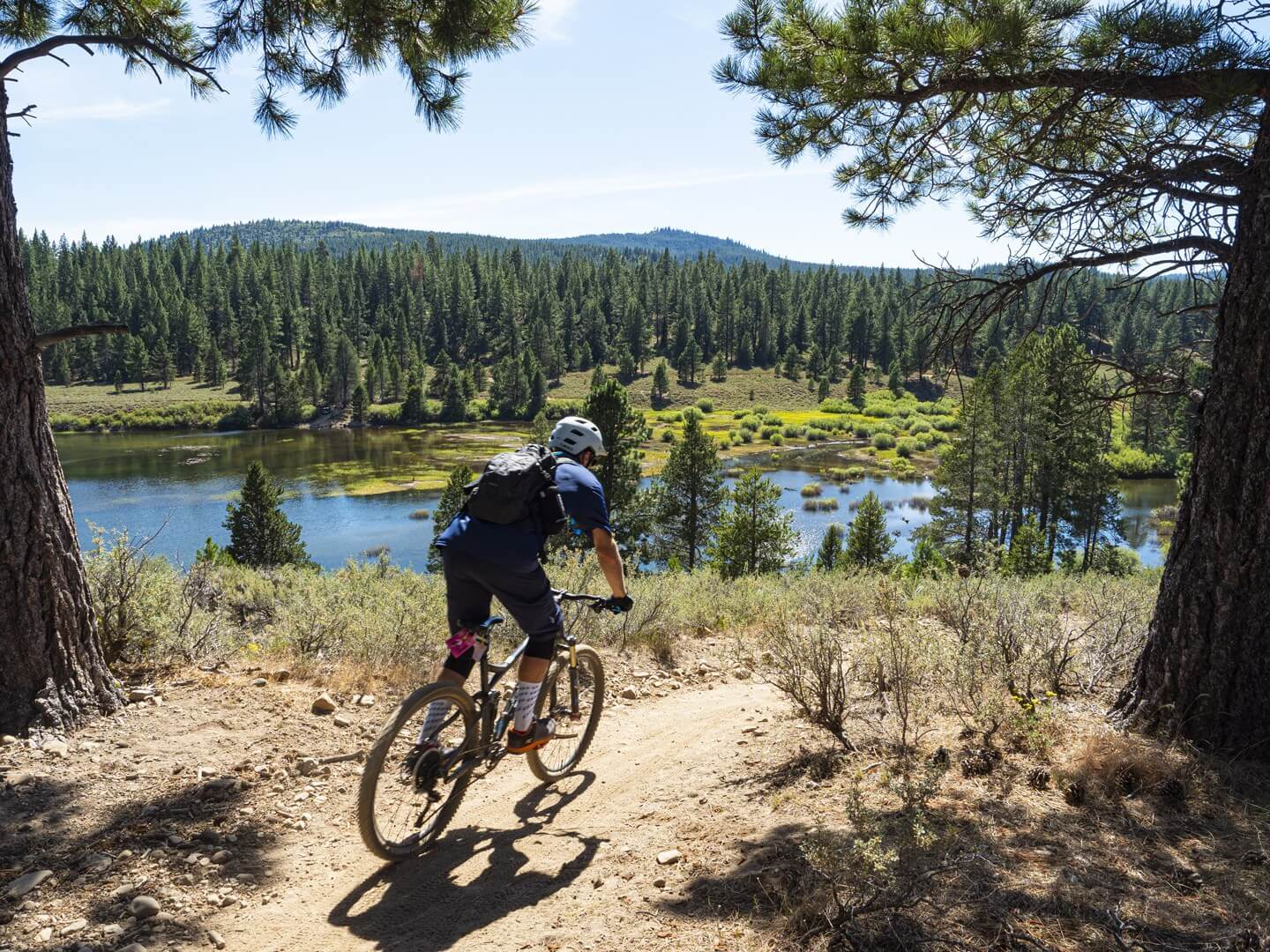 Mountain biker on Truckee Overland Emigrant Trail with lake in the distance