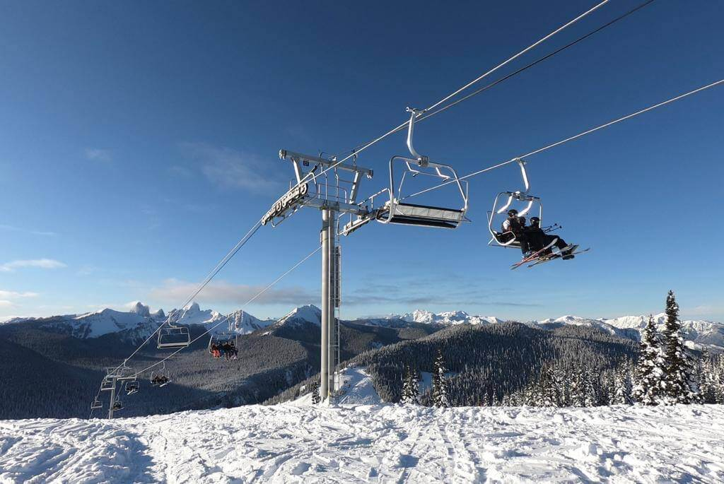 Sunny bluebird day at Manning Park Ski Resort in British Columbia with skiers and snowboarders taking chairlift