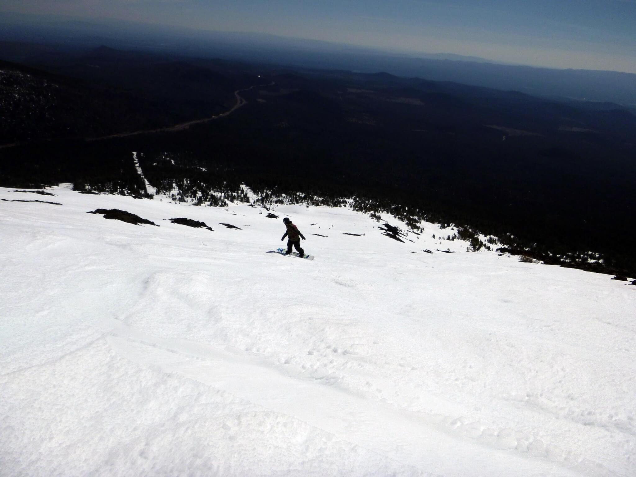 Snowboarding carving corn snow on Cows Face trail at Mt Bachelor