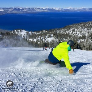 Snowboarder with bright yellow jacket making toe side turn at Heavenly Mountain
