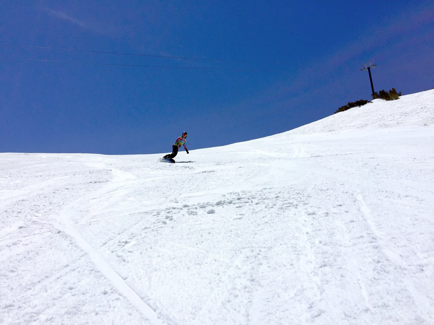 Snowboarder skiing corn snow in June at Mammoth Mountain California