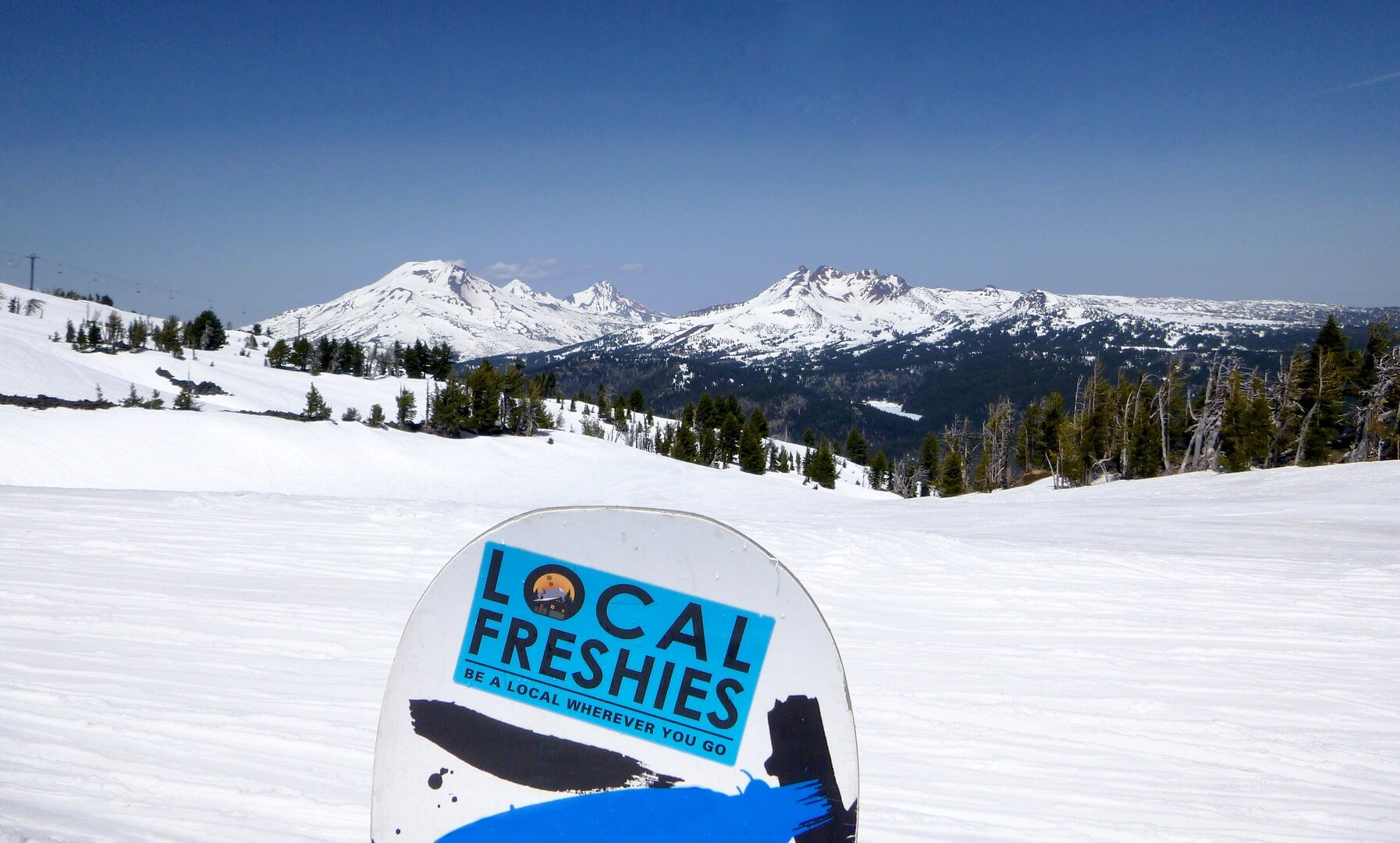 Sunny spring skiing at Mt Bachelor Oregon with Three Sisters Mountains in the distance