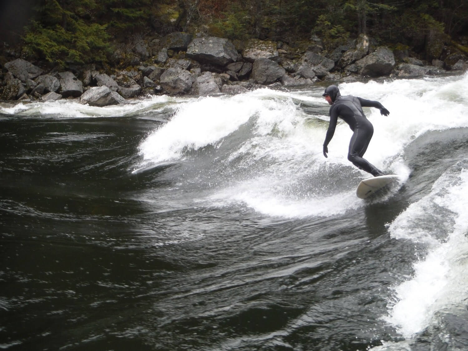 surfer wearing wetsuit taking on the Lochsa Pipeline near Lowell Idaho