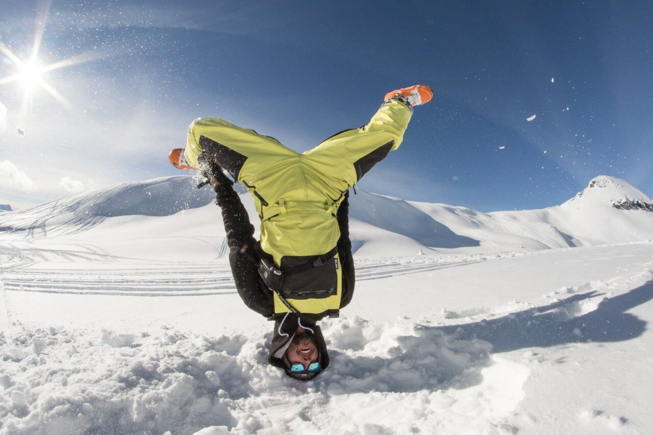 Skier upside down in backcountry wearing ski jacket made in USA