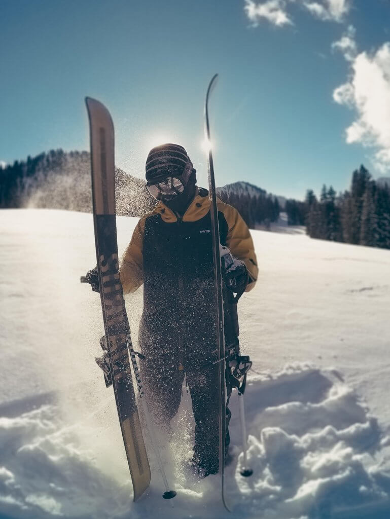 Skier slapping skis wearing NWT3K jacket made in USA
