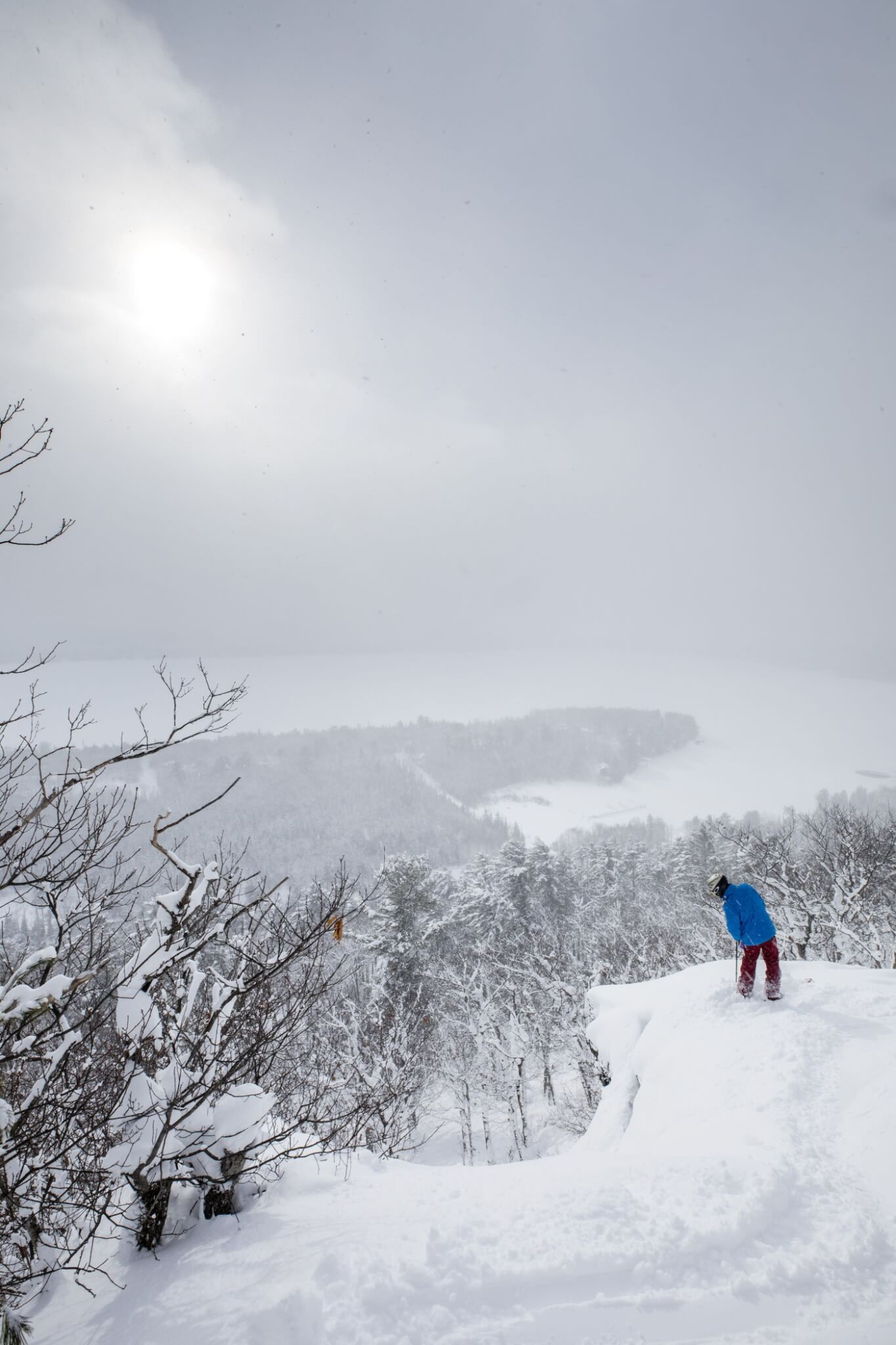 Snowboarder looking over cliff at Mount Bohemia with Lake Superior in the distance