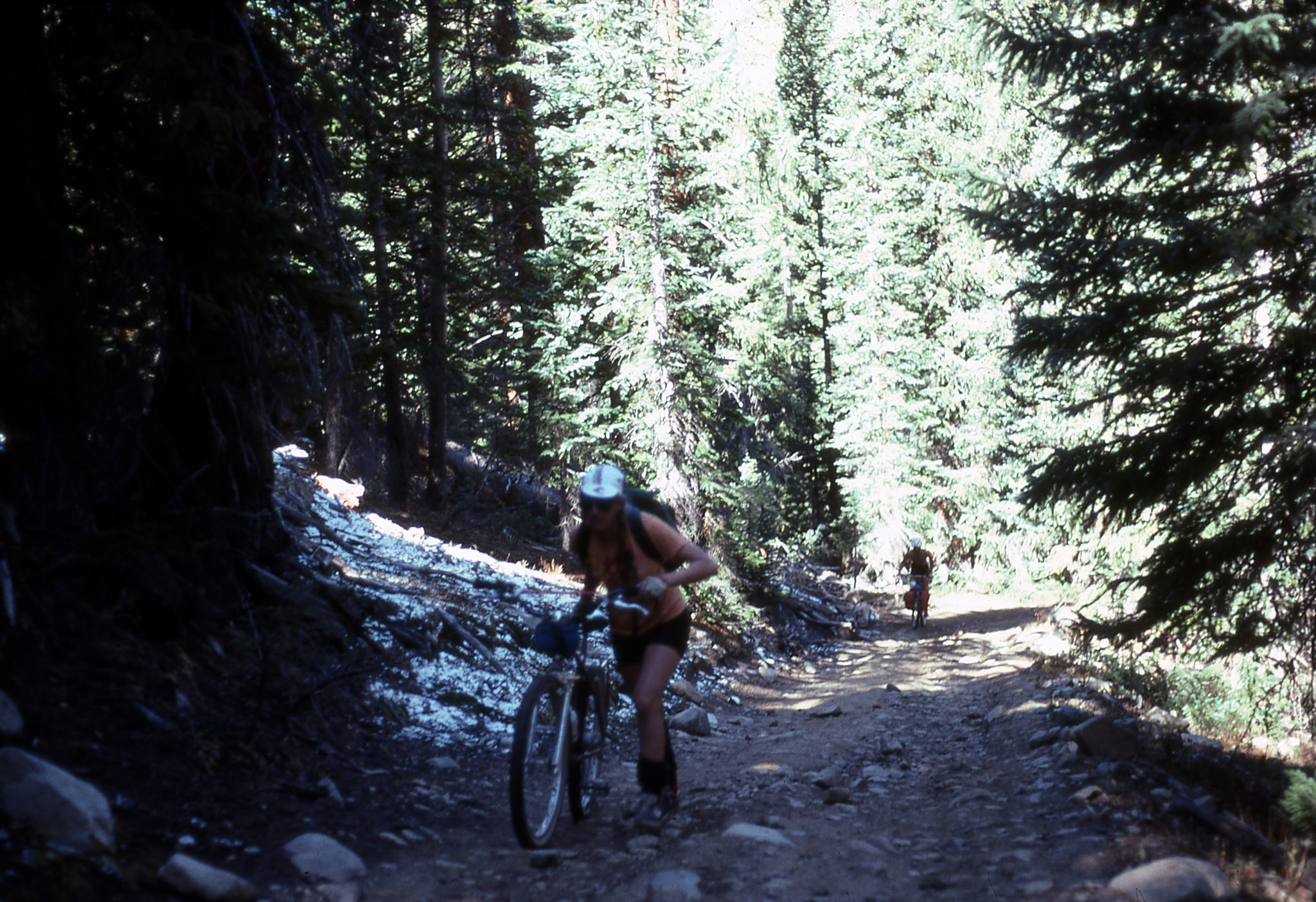 woman hiking up with bike on the Pearl Pass Tour